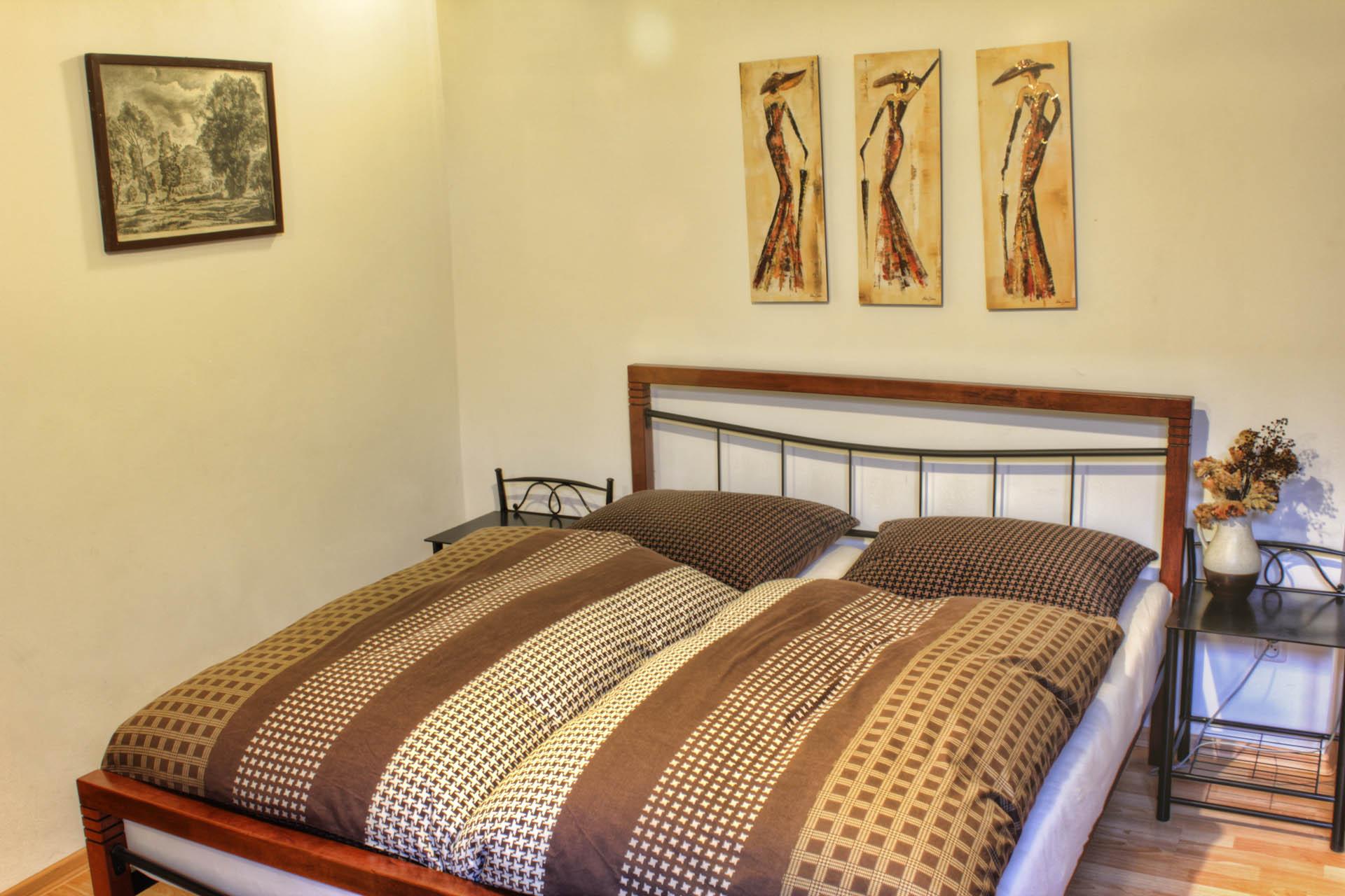 Manželská postel s lůžkovinami pro alergiky a nočními stolky v pokoji Bianka