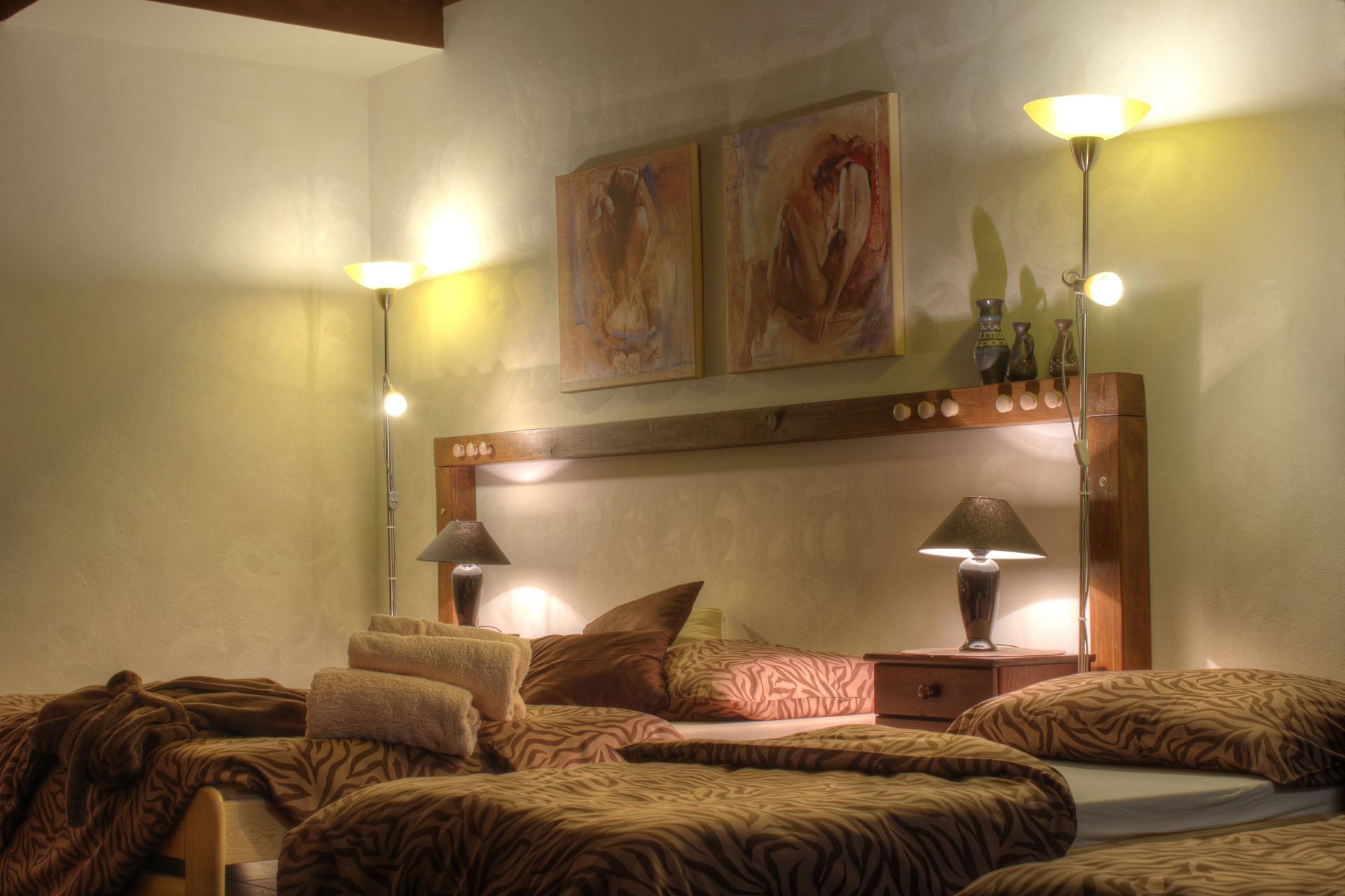 Manželská postel a válenda s nočními stolky a obrazy Talantbeka Chekirova v záplavě světel v pokoji Isabela
