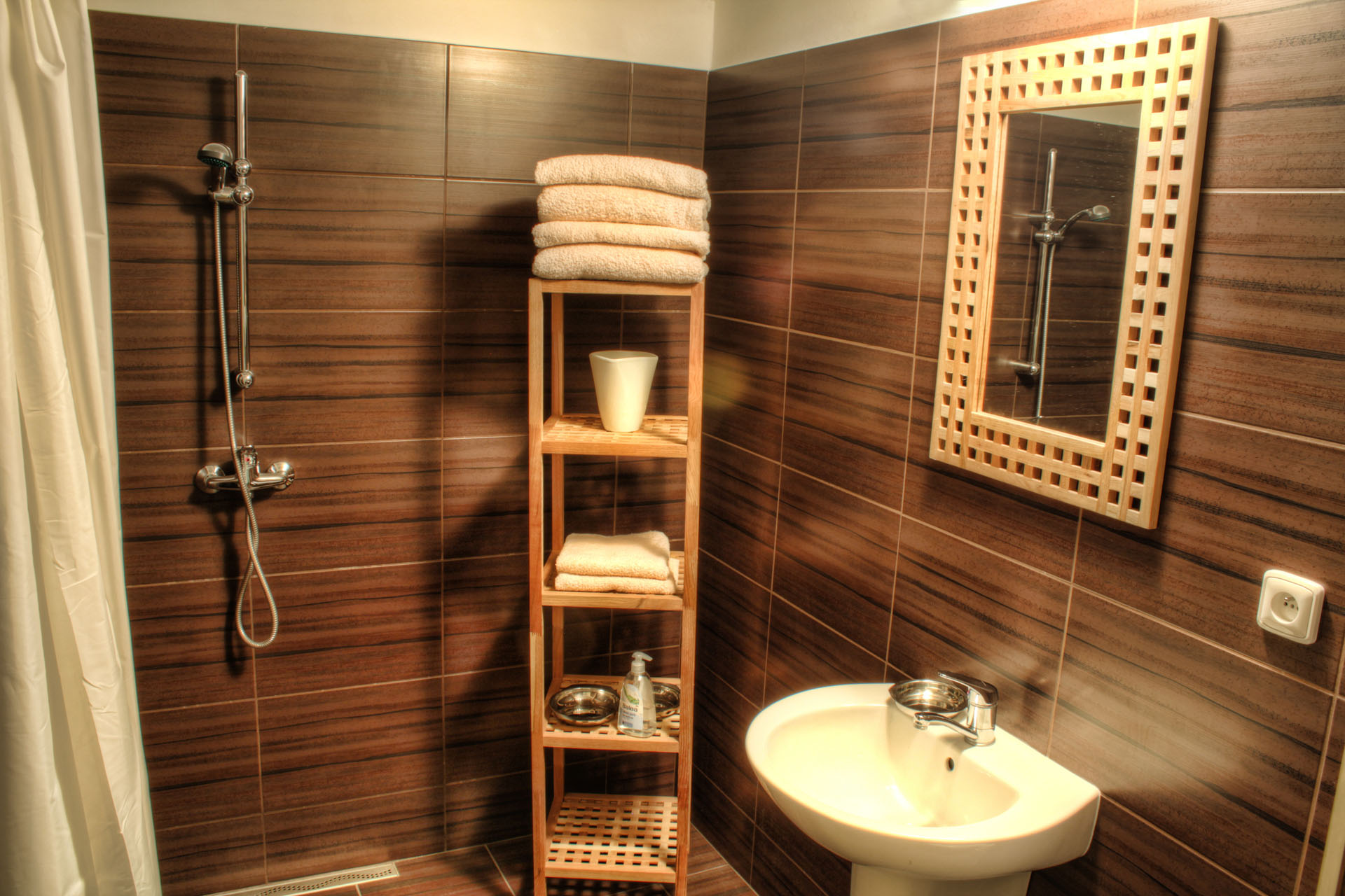 Umyvadlo, sprcha a designový nábytek z teakového dřeva s typickým dekorem obkladů penzionu Komtesa