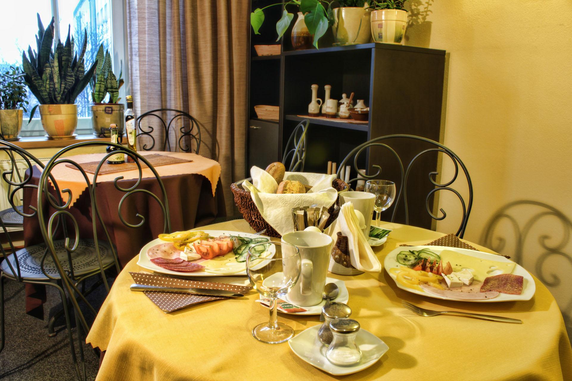 Jídelní stůl s připravenou snídaní pro dva hosty - bohatě obložené talíře a křupavé housky s kávou