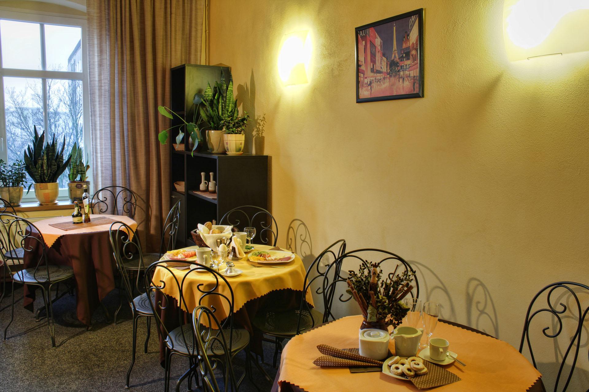 Romantická jídelna s kovovými jídelními stoly a židlemi připravená k podávání snídaní v penzionu Komtesa