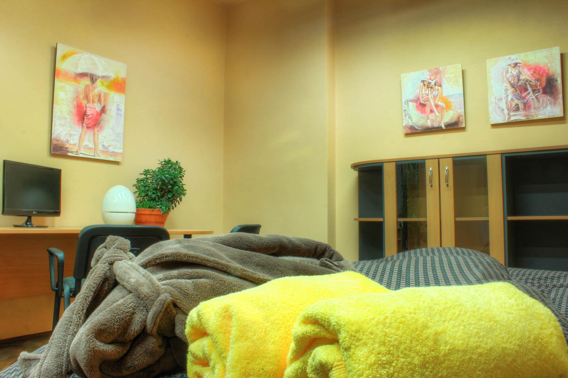 Postel s županem a ručníky, skříňky, originály obrazů a velký pracovní stůl s monitorem v pokoji Ornela