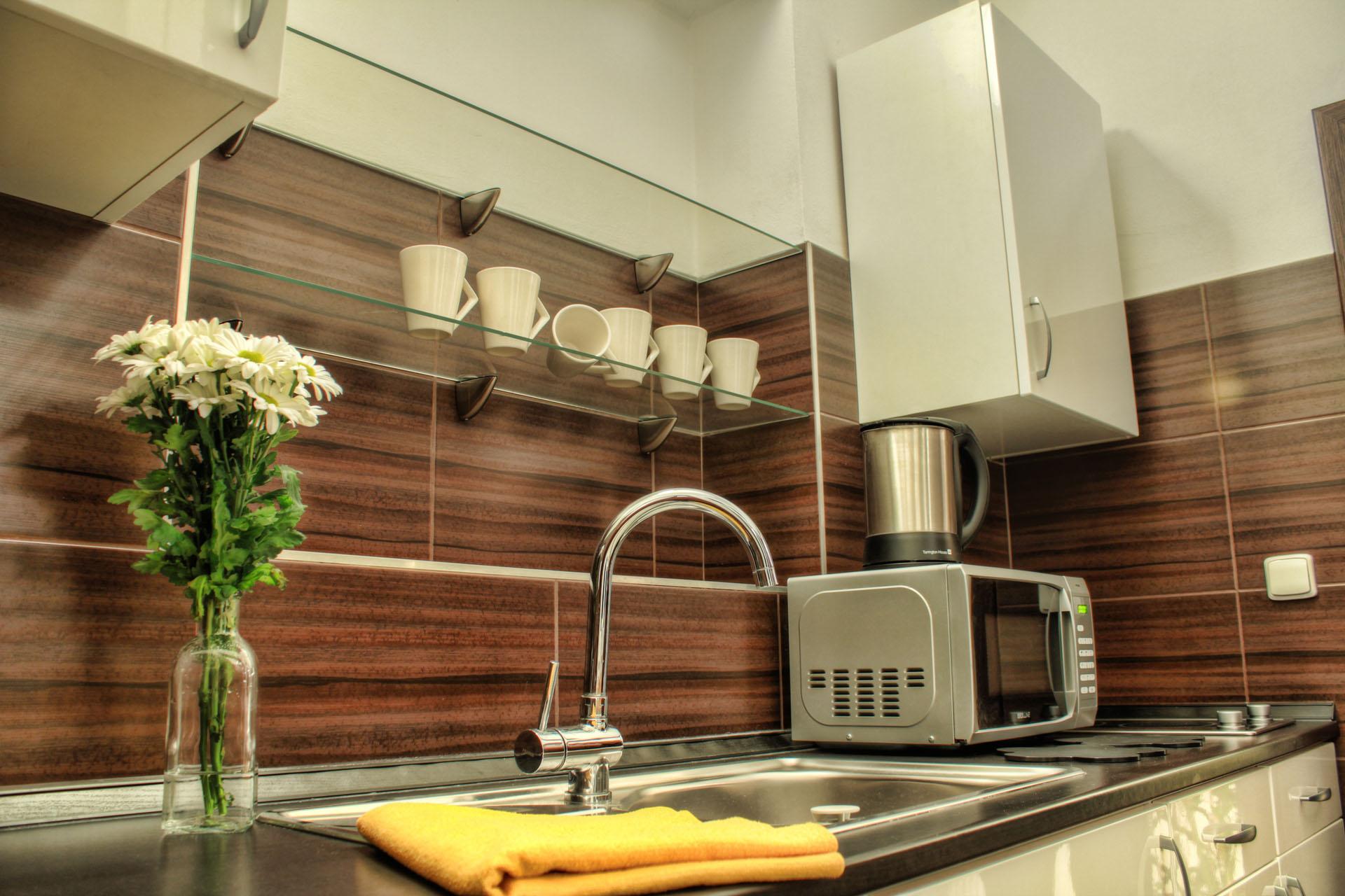 Kuchyňská linka s vázou s květinami, mikrovlnnou troubou a varnou konvicí v apartmánu Ornela a Lukrécie