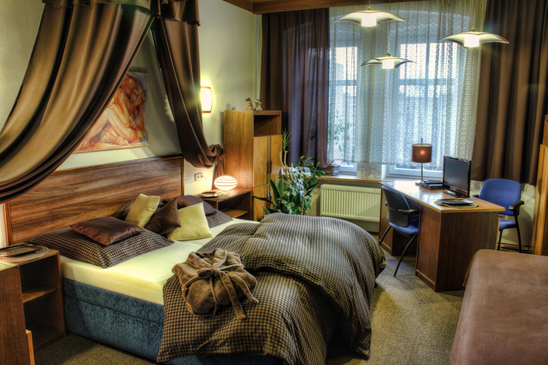 Manželská postel s baldachýnem, nočními stolky, skříňkami, psacím stolem s televizí a květinami v pokoji Rafaela