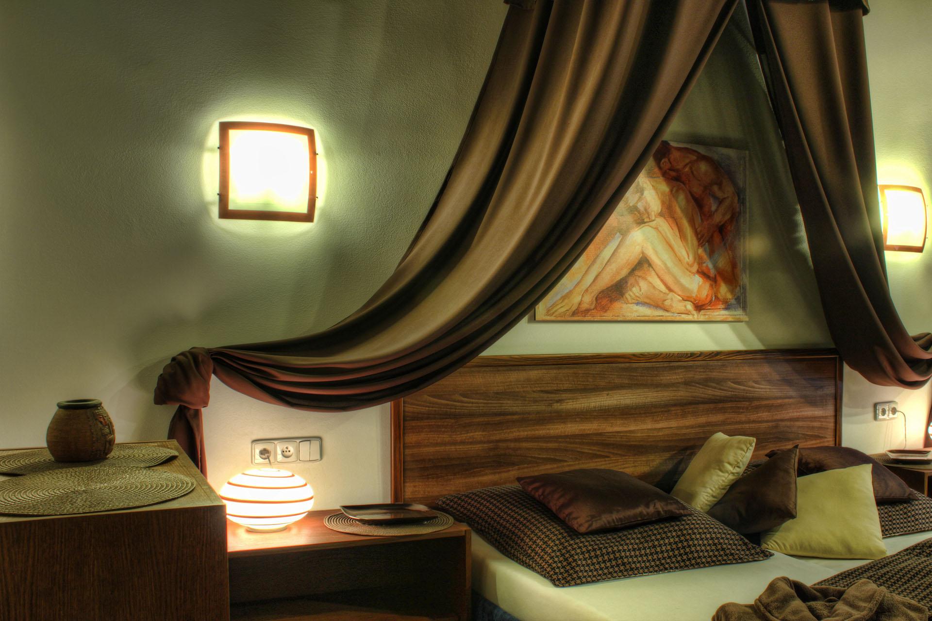 Manželská postel s nočními stolky, skříňkou a originálem obrazu v romantickém osvětlení v pokoji Rafaela
