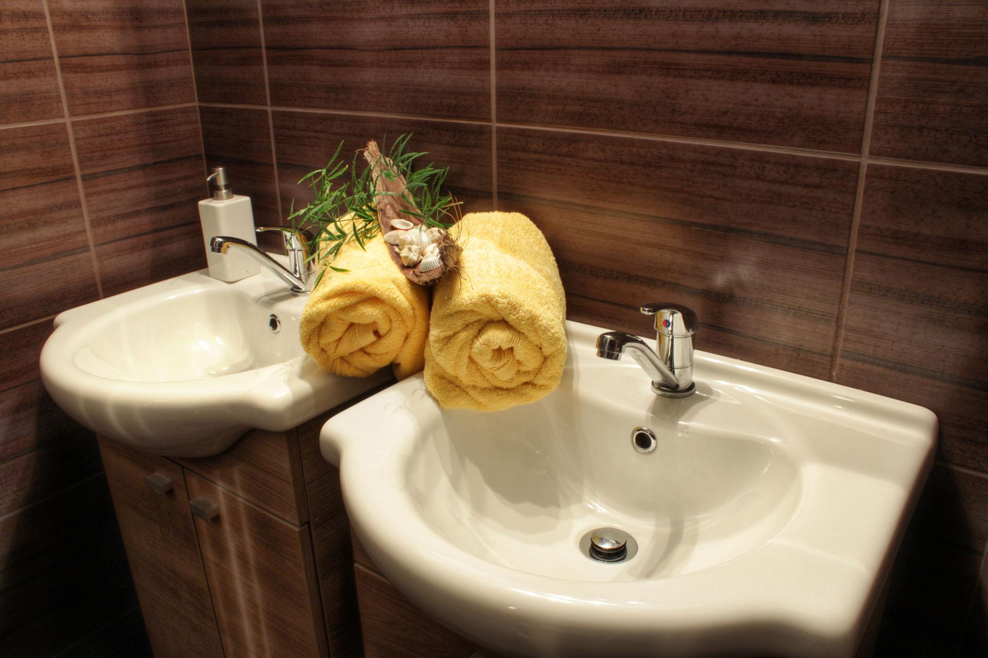 Umyvadla s ručníky, dekorací a typickým dekorem obkladů zdí penzionu Komtesa. Koupelna pokoje Rafaela