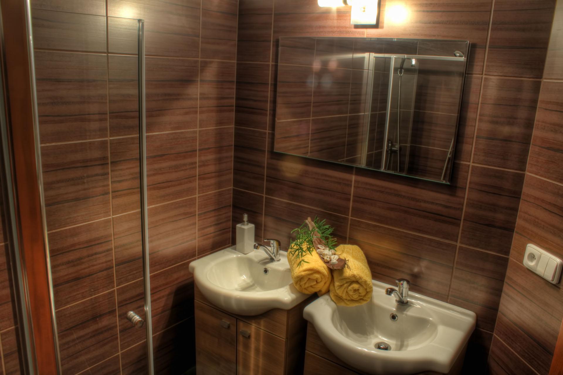 Umyvadla s ručníky, dekorací a osvětleným zrcadlem pokoje Rafaela.