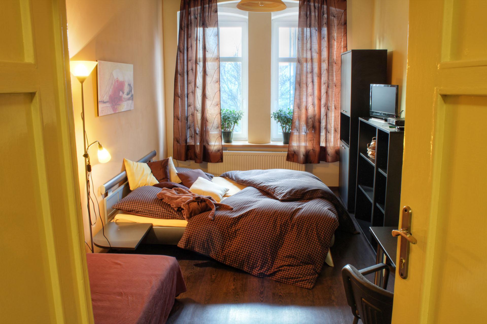 Manželská postel a válenda, úložné prostory, pracovní stůl, obraz Talantbeka Chekirova v apartmánu Sidonie